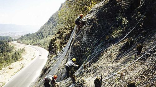 Some workers laying down the rock netting.